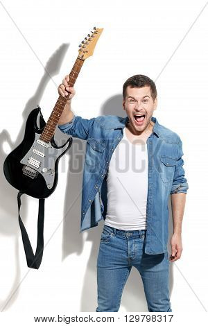 Portrait of young musician shouting with aggression. He is holding a guitar. Man is standing and looking at camera with anger