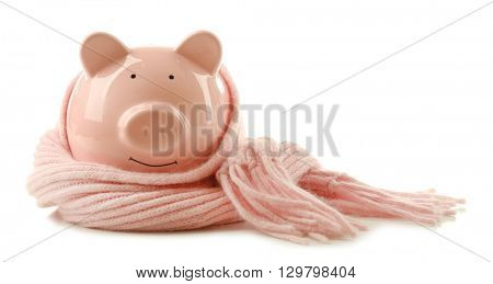 Piggy bank wearing scarf, isolated on white. Saving heating concept