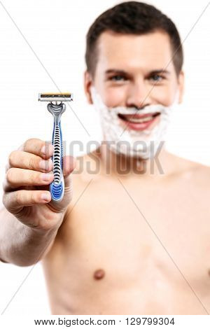 Portrait of handsome young man showing a razor. He is smiling and looking at camera with happiness. Focus on shaver. Isolated