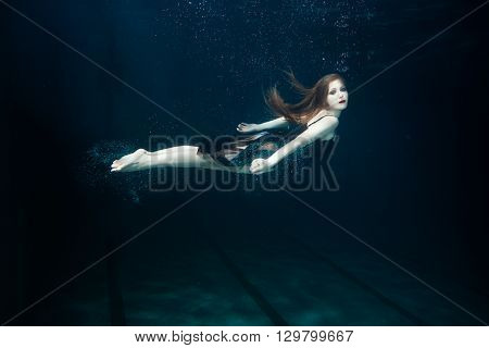 Woman swims underwater with hands clasped around the air bubbles.
