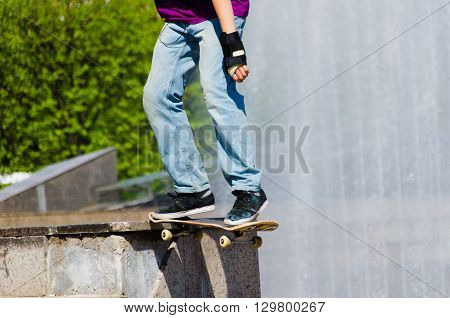 Man making skateboard trick in the street. Boy making grid by skateboard in sunny day. Extreme man skateboarding in a city.