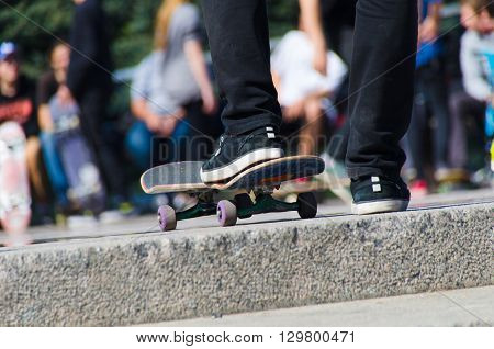 View from back on skateborders leg and skatebord. One leg on skateboard with contest background