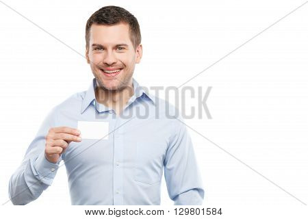 Waist up portrait of attractive young man presenting his visit card. He is standing and looking at camera confidently. Worker is smiling. Isolated and copy space in right side