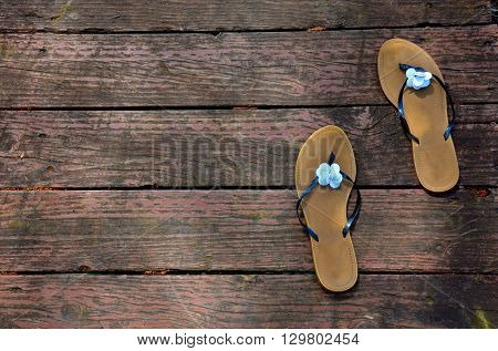 Summertime scene of gently used sandals resting on swimming dock, deck.