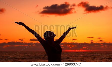 Woman's silhouette over sunset background, happy girl with raised up hands standing on the beach and looking up in the sky, enjoying summer vacation