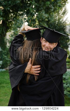 Graduate in the mantle hugs classmate. In the young man's face joyful smile