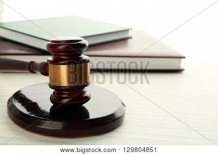 Gavel and books on light wooden background