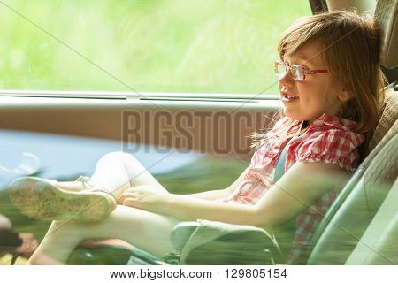 Little girl child kid in glasses with seat belt fastened sitting in car. Holidays vacation trip. Safe summer travel.
