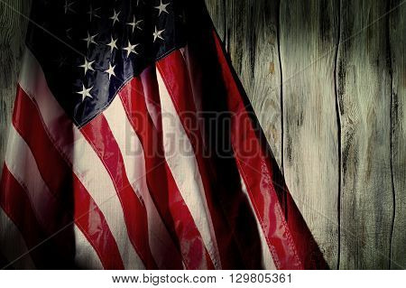 Old flag of United States. Old flag on wooden background. Past times will not return. We've been through a lot.