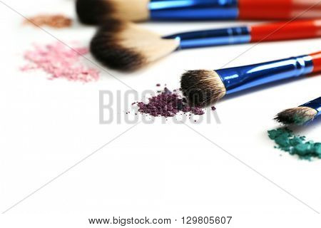 Set of makeup brushes with varicolored powder on white background