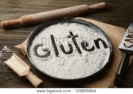 Gluten word written with flour on baking utensil over wooden table