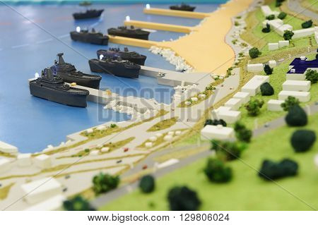 Warships wharf scale model, layout of army naval base, miniature of military harbor with small models of ships, piers, docks, buildings and port driveways, selective focus