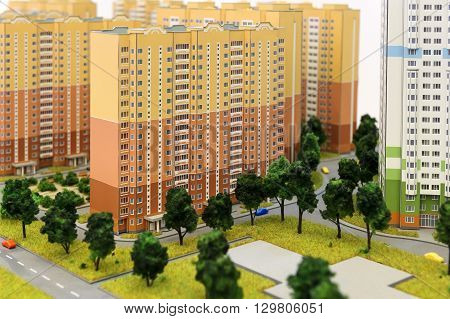 Apartment buildings scale model, residential district layout, mock-up of colorful prefabricated houses with children's playground, trees, grass, roads, sidewalks, driveways, selective focus