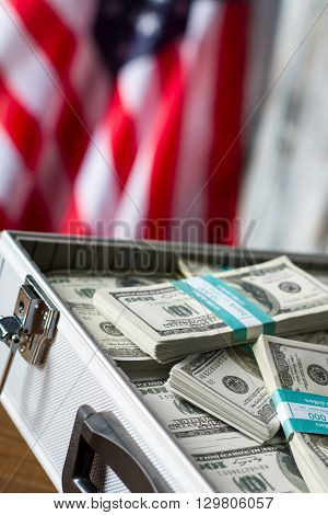 Opened case with dollar bundles. Cash near american flag. Freedom and opportunities. Richness and glory.