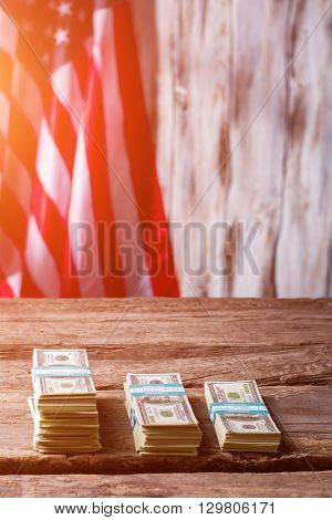 American flag and dollar bundles. Bundles of cash beside flag. Capital is growing. Earn and multiply.
