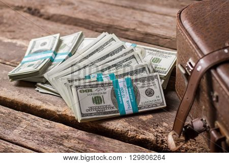 Bundles of dollars and case. Brown suitcase near american dollars. Tickets to the future. Chance of a lifetime.