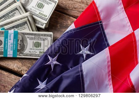 Dollar bundles and American flag. Bundles of cash beside flag. Wealth and opportunities. Income of average citizen.