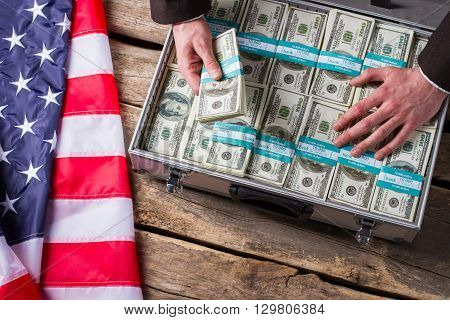 Hand touches dollars in suitcase. US flag laying beside cash. Better hide it away. Greed and fear.