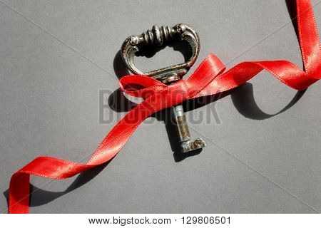Vintage key with  a red ribbon on a grey background