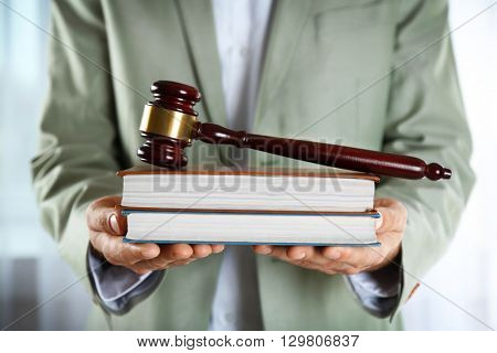 Man holding books with wooden gavel closeup