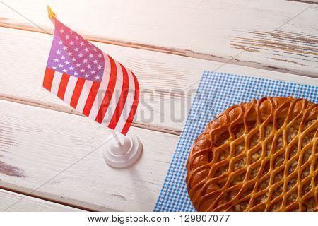 USA flag, pie and napkin. Pie laying beside table flag. Breakfast of true patriot. Traditional sweet pie with apples.