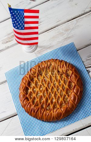 US flag and round pie. Pie on napkin beside flag. Fresh pastry on white table. Traditional pie with fruit filling.