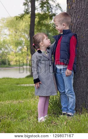 Little boy and girl on a sunny day standing on green grass near tree looking at each other