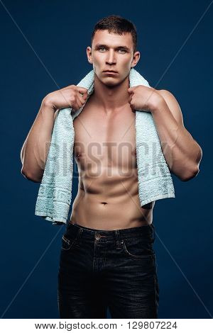 Muscular man in jeans with a naked torso, cubes, holding the towel around neck after a workout. Sports portrait in Studio on a blue background