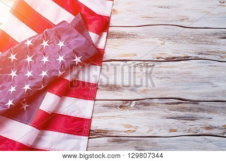 Crumpled flag of US. US banner on wooden background. National flag in the sunlight. Peace, love, and prosperity.