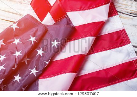 Creased flag of USA. USA national flag in sunlight. Banner laying on wooden shelf. Peace, prosperity and future.
