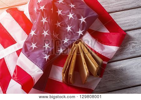 American flag and old book. Flag and book under sunlight. Rights and freedoms of nation. History, culture and traditions.