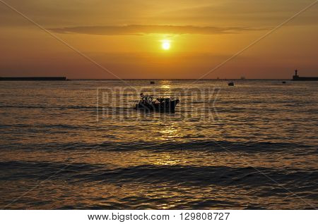 Silhouette of a boat on the background of a bright sunset in a bay