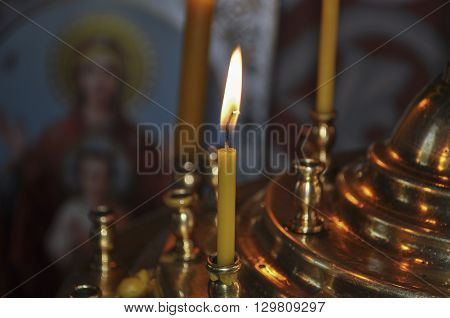 bright burning candle in gold plated chandelier