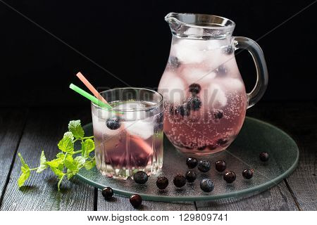 Cold refreshing drink with blueberries black currants juice soda water and ice in a jug and a glass of cocktail straws on a dark background. Selective focus
