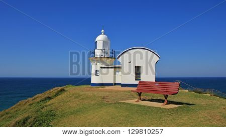 Small old lighthouse on a hill in Port Macquarie. Bench. Scene in Australia.