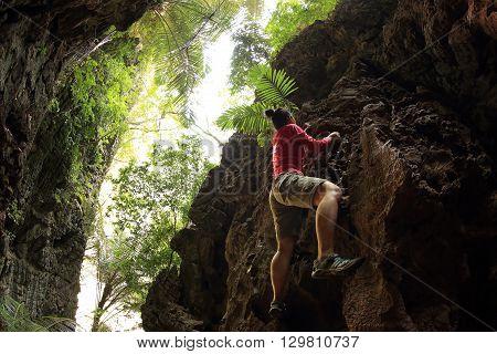 young woman rock climber climbing at seaside mountain rock