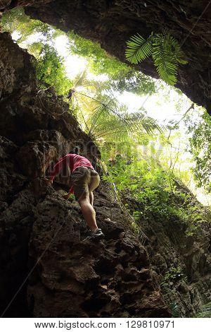 young woman rock climber climbing at seaside mountain cliff