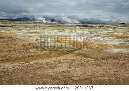 Steam escapes in the distance from an active volcano with red earth and sulphur. Mountains and a dark blue sky in the distance.