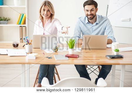 Sit down please. Cheerful young woman is pointing her arm on chair and smiling. Man is sitting at desk near her with joy
