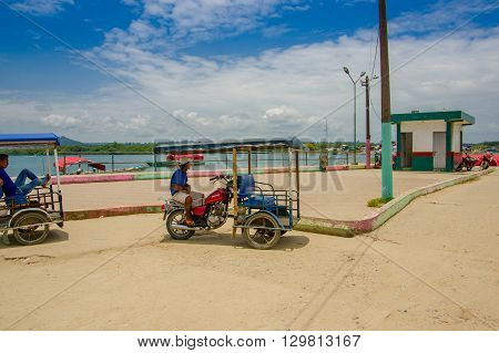 Muisne, Ecuador - March 16, 2016: Local tuktuk driver sitting in his vehicle next to ocean waiting for passengers on a beautiful sunny day.