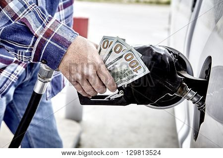 Mans Hand Holding Cash While Refueling Vehicle