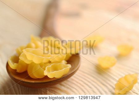 Dry gnocchi pasta in wooden spoon on a table