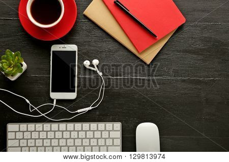 Workplace with mobile phone, peripheral devices and stationery on dark wooden table