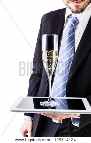 a businessman wearing a suit and a tie using a tablet as a tray for a glass of champagne isolated over white