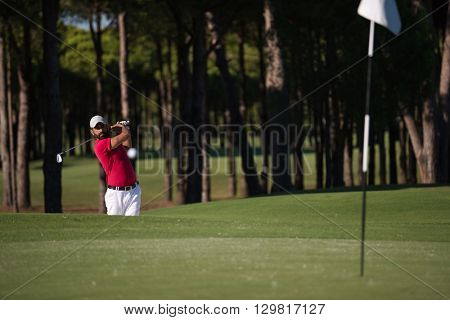 golf player shot ball from sand bunker at course