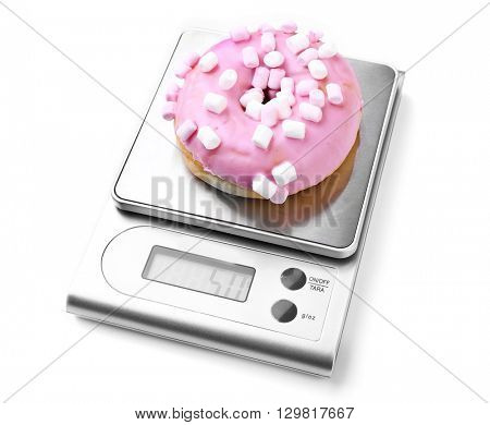 Sweet doughnut on digital kitchen scales, isolated on white