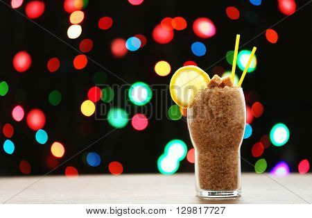 Glass with granulated brown sugar on dark bokeh background