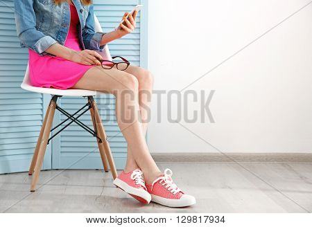 Young fashion blogger with her smart phone sitting on chair indoors