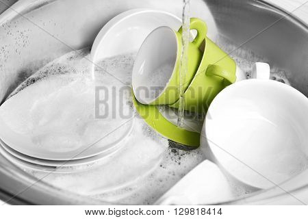 Pile of dishes in sink closeup