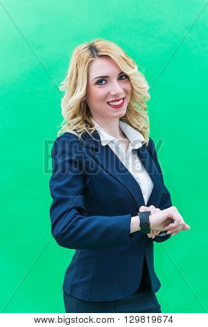 Young woman using smartwatch standing. Wearing blue suit she has blonde hair and blue or blue eyes on a white background. Smile always smiling.